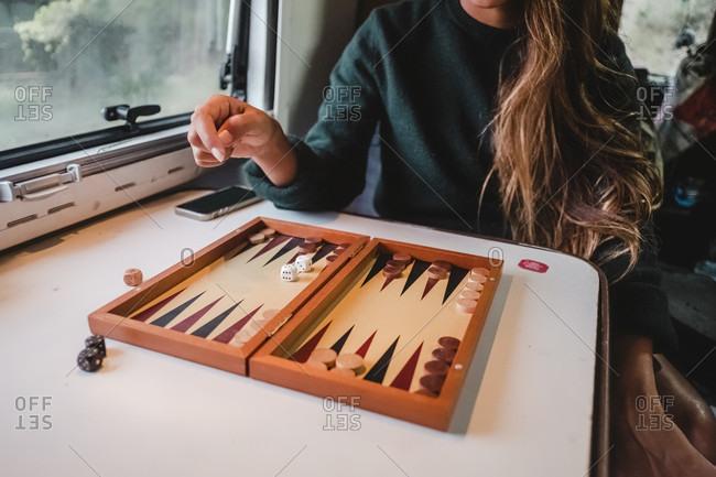 Woman playing backgammon in camper van, Costa Brava, Catalonia, Spain