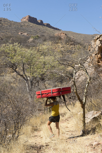 August 22, 2014: Woman carrying exercise mat at Mount Etjo during sunny weather, Otjozondjupa, Namibia