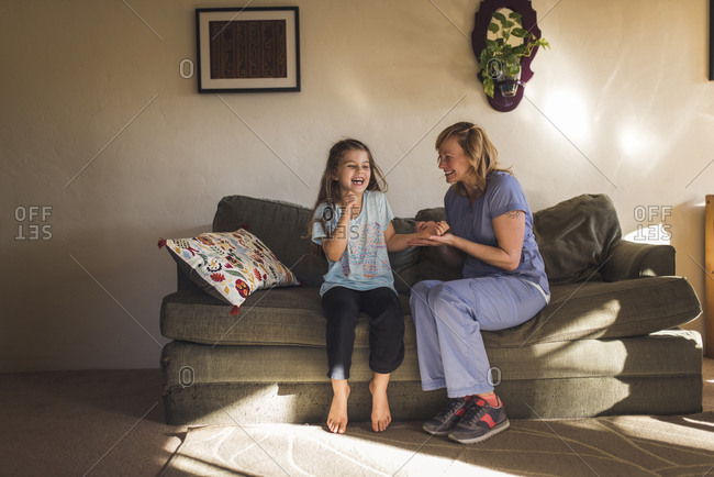 Happy female doctor checking pulse of girl while sitting on sofa at home