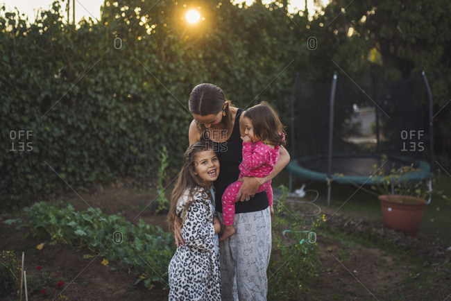 Mother with daughters standing in yard during sunset