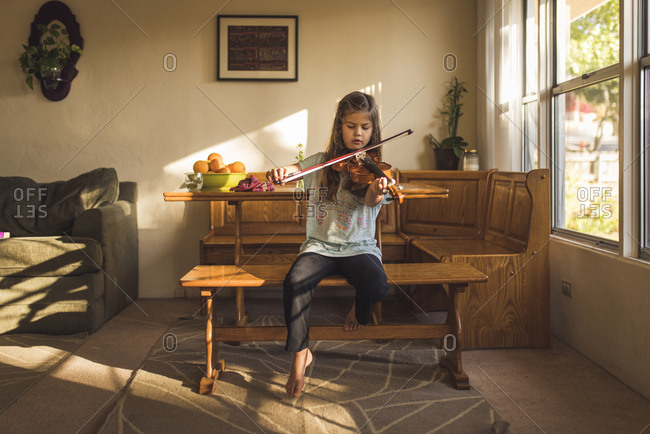 Girl playing violin while sitting on wooden seat at home