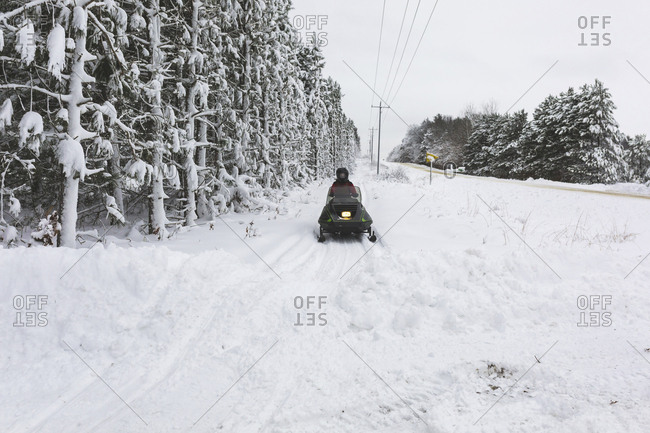Rear view of teenage boy driving quadbike on snow covered field against sky in forest