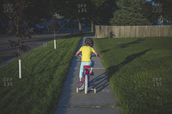 Rear view of girl riding bicycle on footpath at park