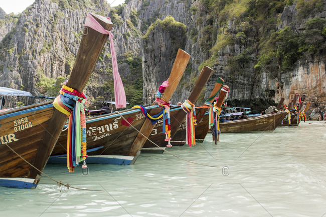 Thailand - April 6, 2017: Cropped image of longtail boats moored on sea by mountain