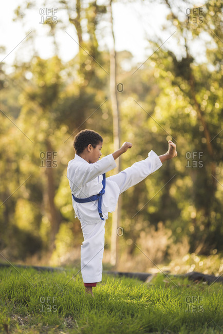 Side view of boy practicing karate on grassy field at park