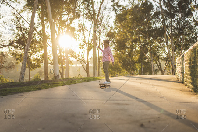 Side view of boy skateboarding on footpath at park during sunset