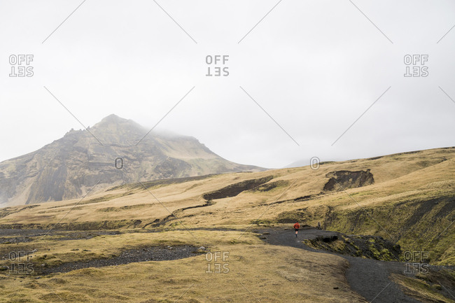 Mid distance view of hiker running on mountain against sky