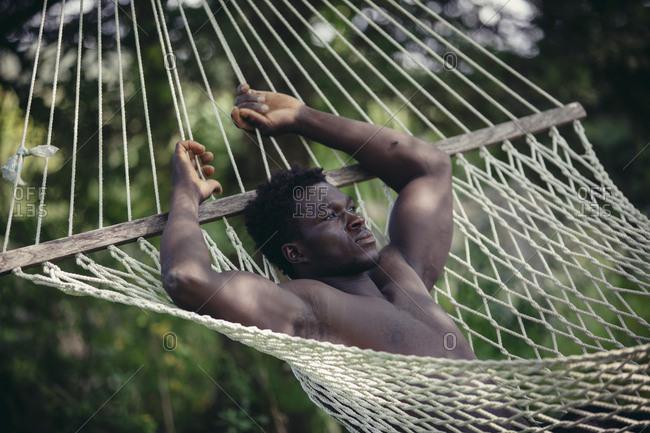 Thoughtful shirtless young man relaxing in hammock