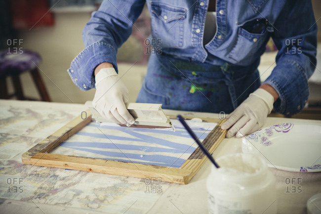 Midsection of craftswoman using squeegee while working at workshop