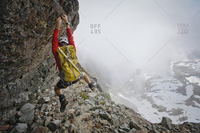 Hiker with backpack climbing mountain