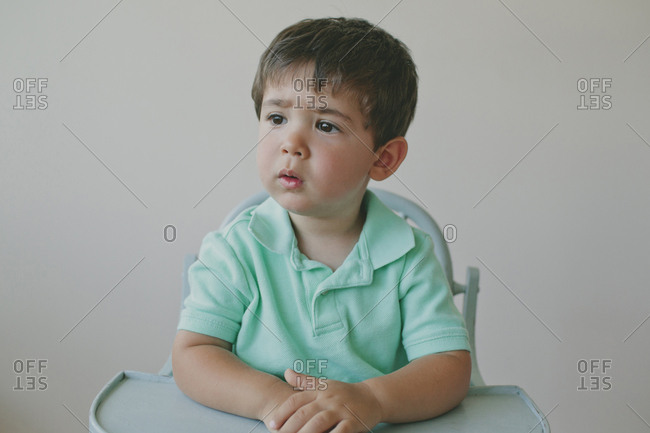 Thoughtful baby boy looking away while sitting on high chair against gray background