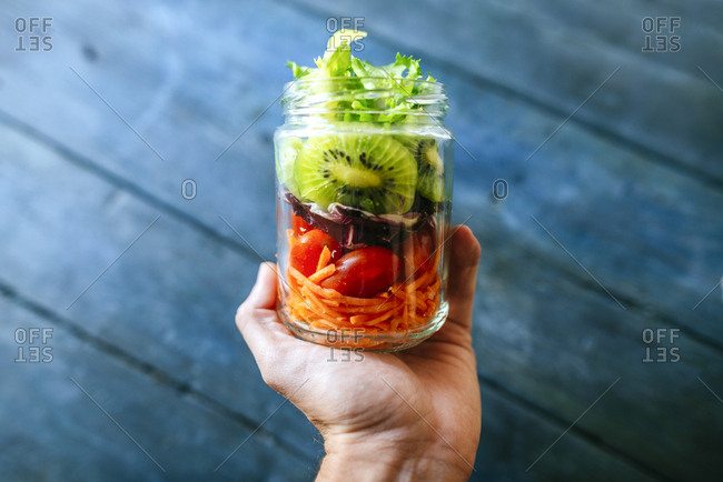 Hand holding jar with salad