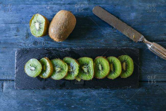 Sliced kiwi on blackboard plate on blue table