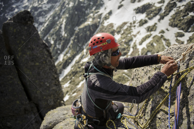 Galayos, Spain - April 23, 2013: Climber managing ropes in the belay of a multi pitch alpine route