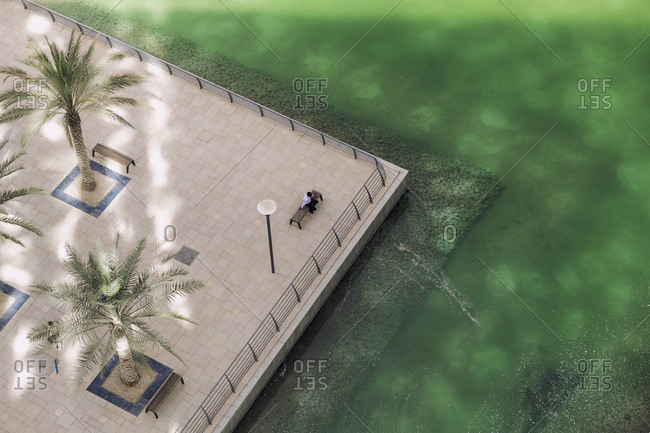 Person sitting on bench seen from above in Jumeirah Lake Towers, Dubai
