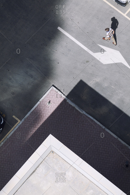 Man walking in parking lot seen from above in Jumeirah Lake Towers, Dubai