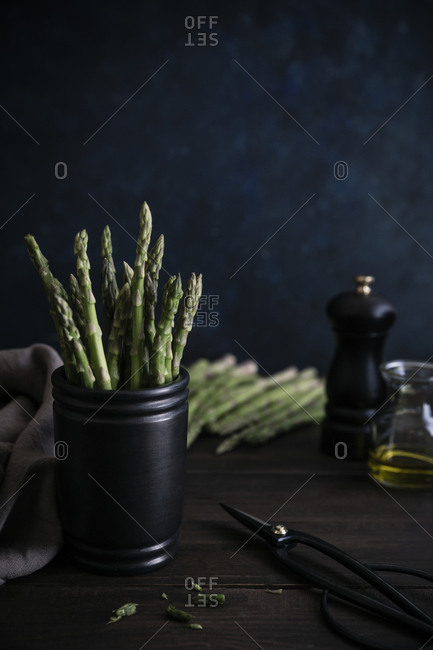 Raw asparagus in a cup on wooden table