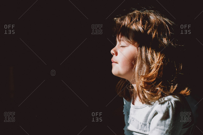 Young girl enjoying warmth of sun on face with eyes closed