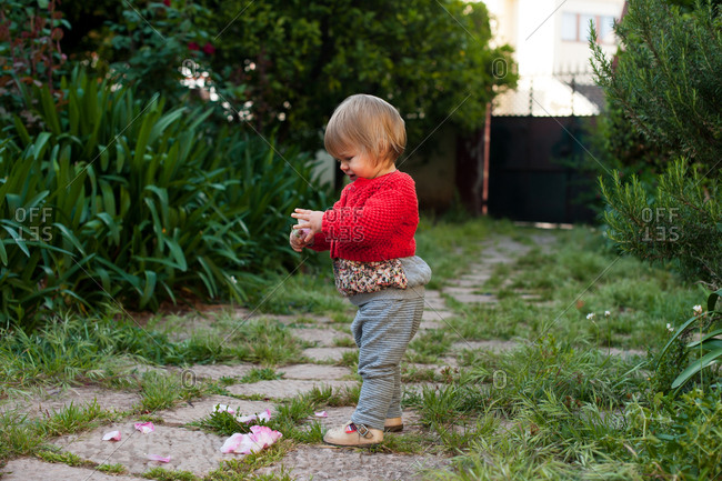 Baby girl playing with flower petals in yard