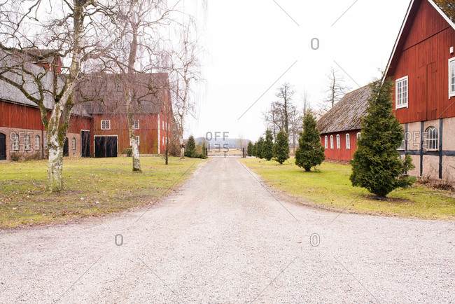 Looking down gravel driveway of complex of traditional red timbered buildings