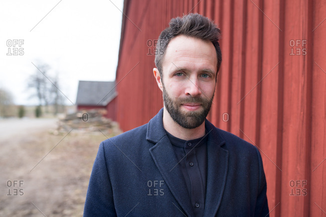 Portrait of young bearded man standing by red wall