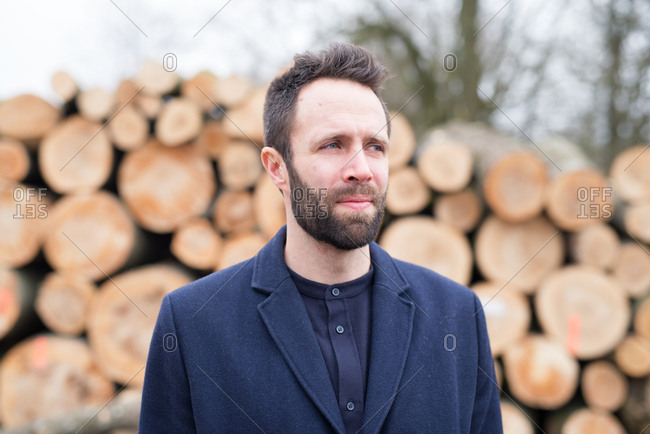 Portrait of young man with beard in front of stack of logs