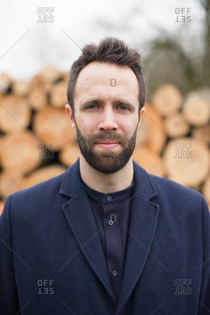 Portrait of young bearded man in front of logs in lumberyard