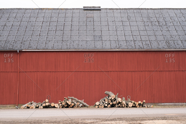 Small pile of logs stacked outside red walled warehouse