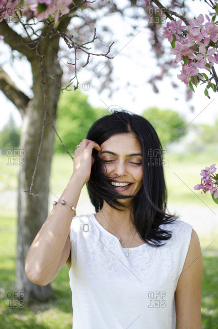 South Asian woman under a blossom tree