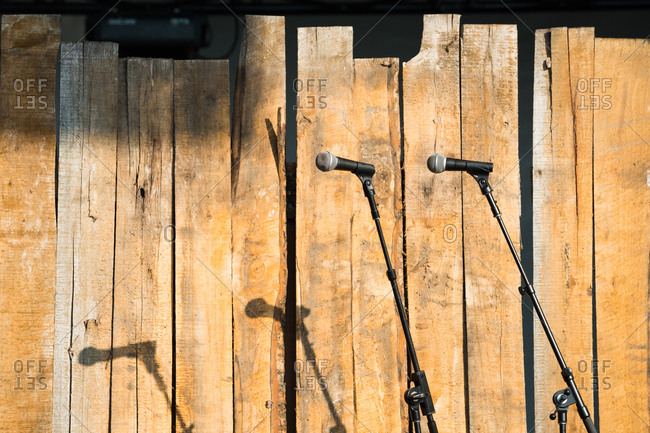 Microphones lined up and ready in front of a wooden fence