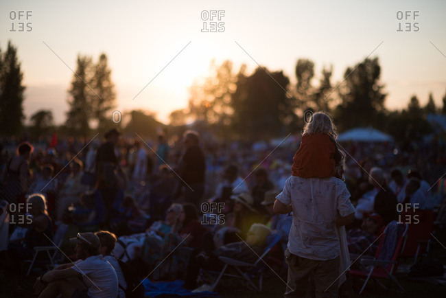 Festival goers young and old soaking up the music at sunset