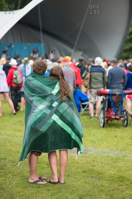 A couple wrapped in a blanket listening to music