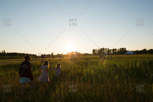 April 18, 2018: Walking through grassy prairie field in soft summer sunlight