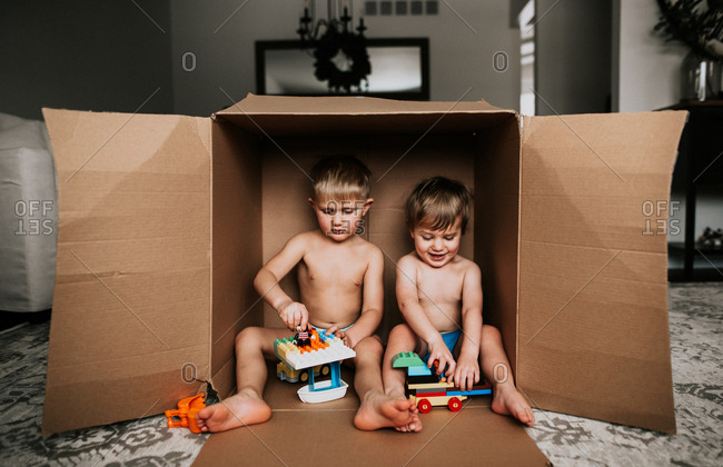 Two boys sitting in a large cardboard box playing with their toys
