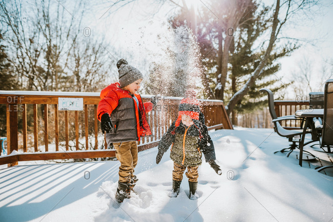 Two boys throwing snow up in the air in morning after fresh snow fall
