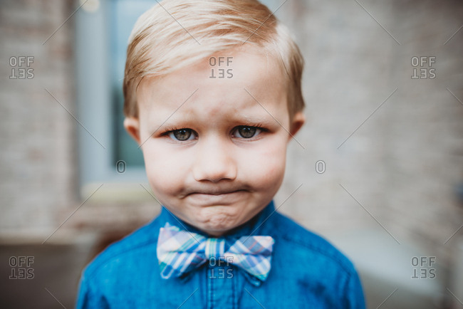 Little boy very annoyed at having to wear best clothes for special occasion