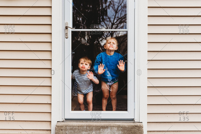 Two boys standing inside pressing lips and nose against glass door