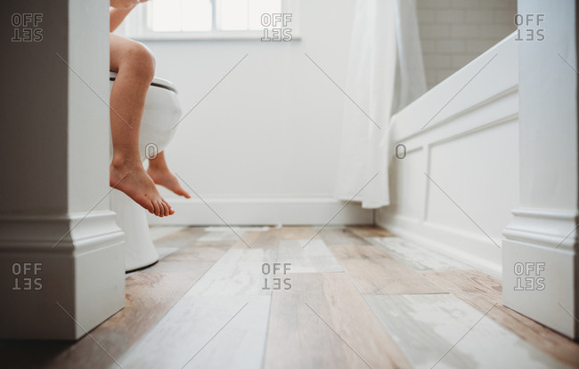 Bare feet and legs of toddler sitting on toilet