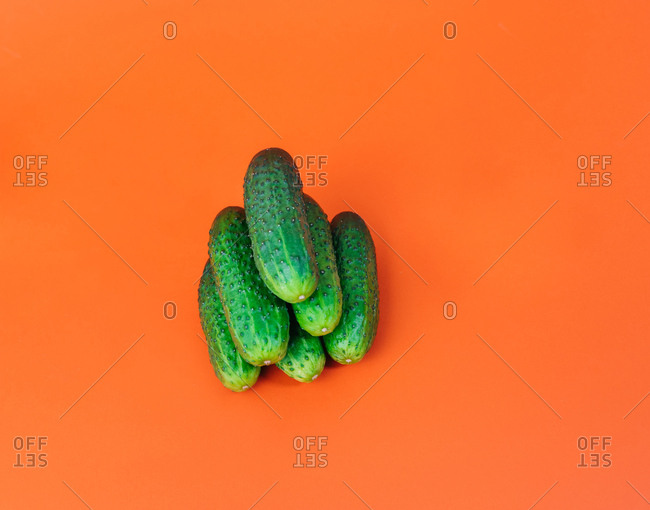 Vibrant cucumbers on a colorful orange background