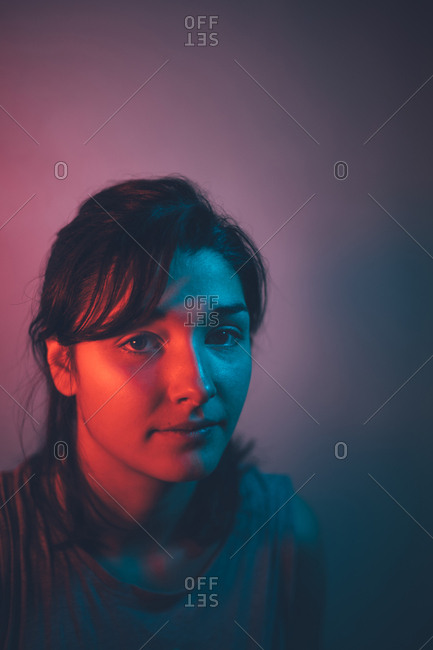 Portrait of a beautiful girl in blue and red lights