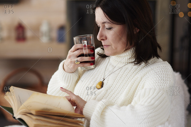 Mature woman with a hot drink reading a book