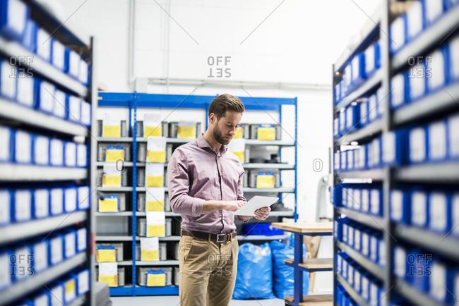 Businessman using tablet in storage