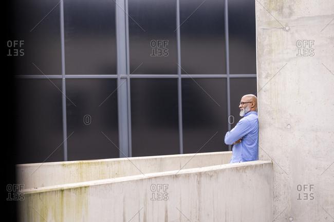 Pensive businessman leaning against concrete wall