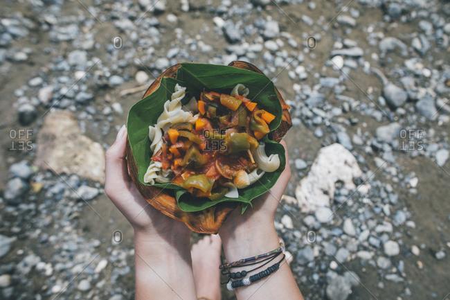 Hands holing Cuban dish in a banana leaf