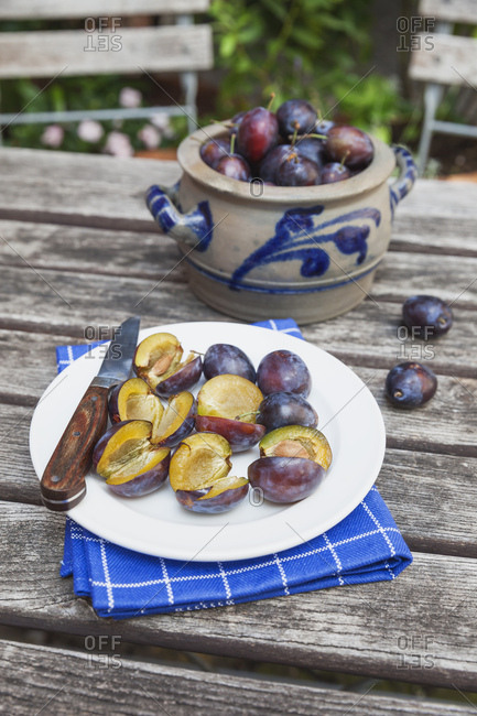 Fresh plums in stoneware pot and chopped plums on plate