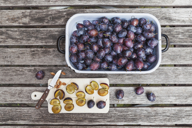 Fresh plums in casserole and chopped plums on chopping board