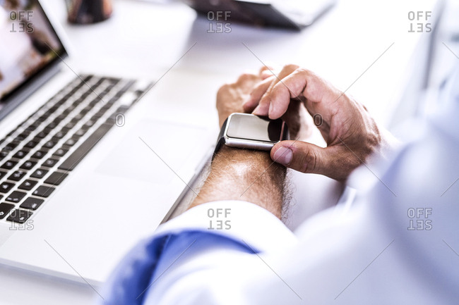Close-up of businessman at desk with laptop using smart watch