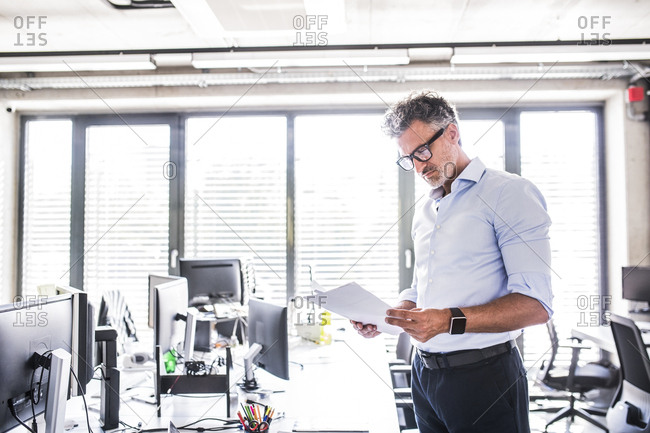 Mature businessman standing in office reading documents