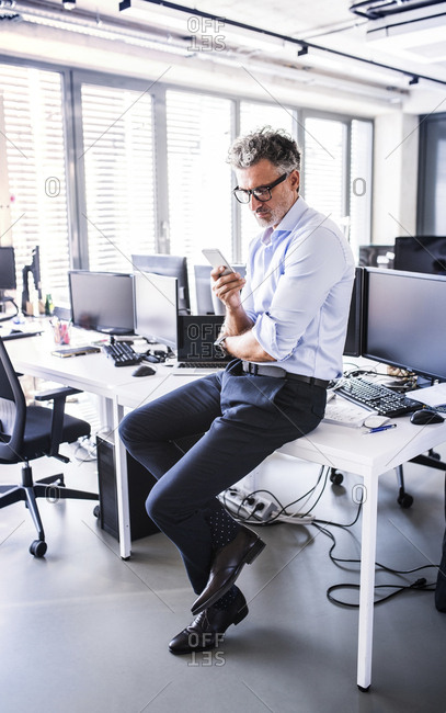Mature businessman sitting on desk in office using smartphone