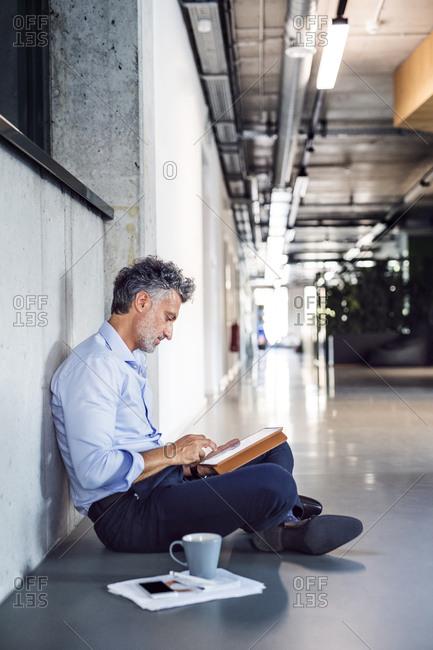 Mature businessman sitting on the floor using tablet